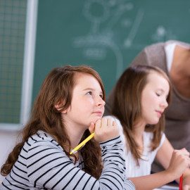 Thinking female student with her classmate listening to teacher in school classroom